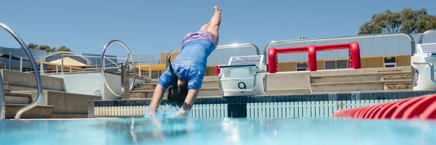 A young woman dives headfirst into a pool safely