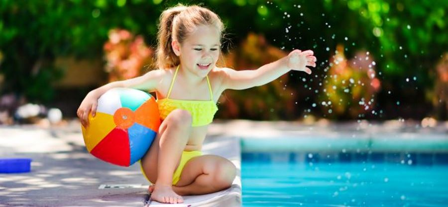 A young girl by the pool holding a beach ball and splashing the water