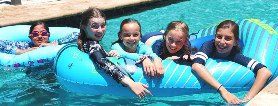 Five girls on floating toys in a swimming pool