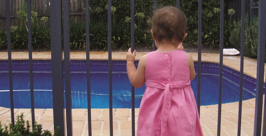A toddler girl wearing a pink dress standing by a black metal pool fence