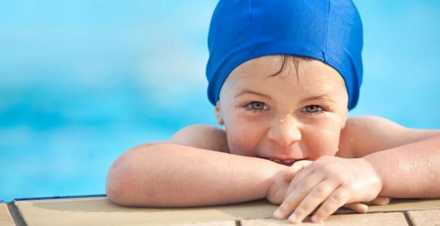 A little boy leaning on the edge of a pool wearing a blue swimming cap