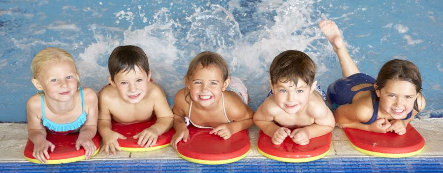 Five children leaning on the edge of a pool with kickboards, kicking their legs