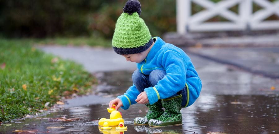 A child rugged up in winter clothes playing with rubber ducks in a puddle