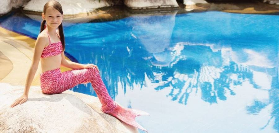 young girl wearing a pink mermaid tail and sitting by the pool on a rock