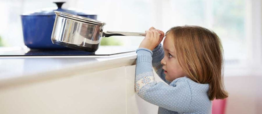 A toddler girl holding the handle of a pot and just about to pull it off the stove