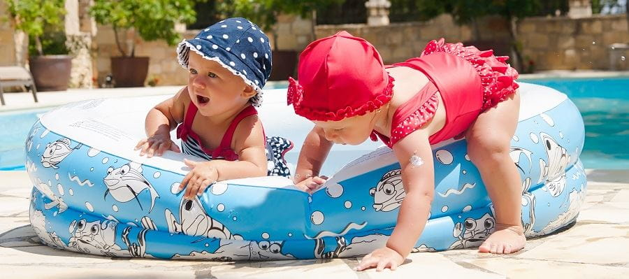 Two toddlers playing in and around a paddle pool, with one almost falling over
