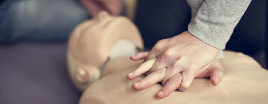 close of person performing chest compressions on a manikin