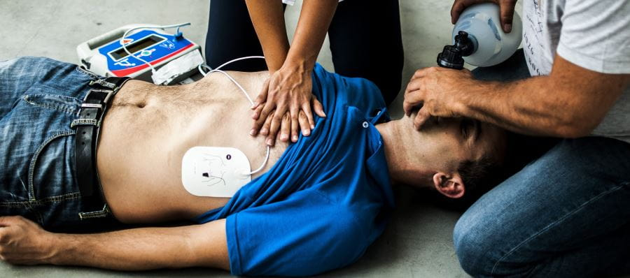 Two people using a defibrillator and performing CPR