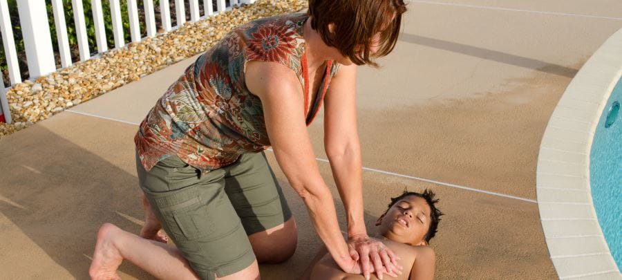 Lady giving CPR to unconscious boy