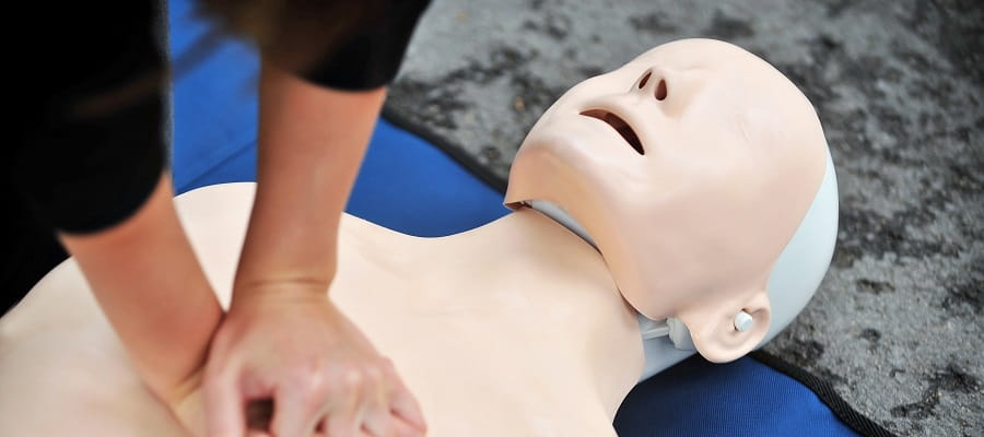 close up of someone performing compressions on a CPR manikin