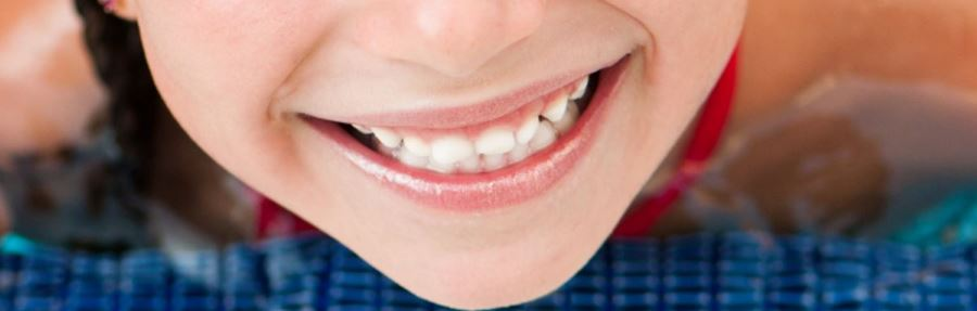 a close up image of a girls mouth as she smiles with teeth showing