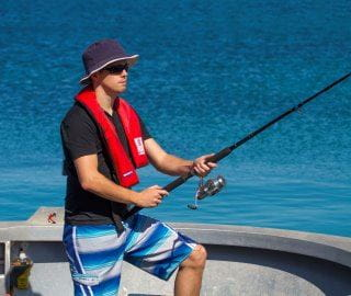 Image of a man fishing from a boat, wearing a hat, sunglasses and a lifejacket