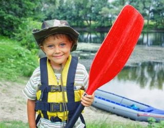 image of young boy standing by a river, wearing a lifejacket and carrying an oar, inflatable boat in the background