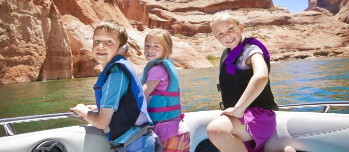 3 children on a boat wearing lifejackets