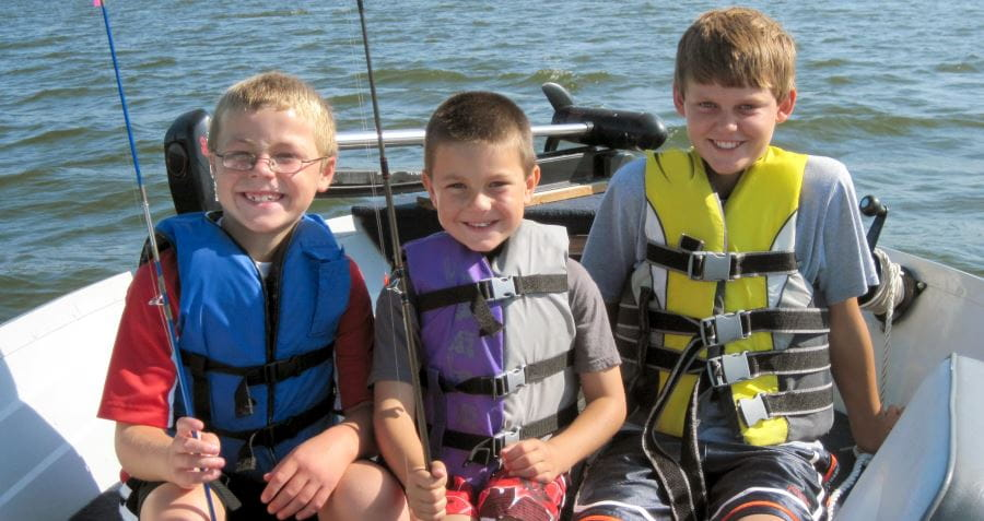 Three young boys wearing lifejackets, in a boat, holding fishing rods