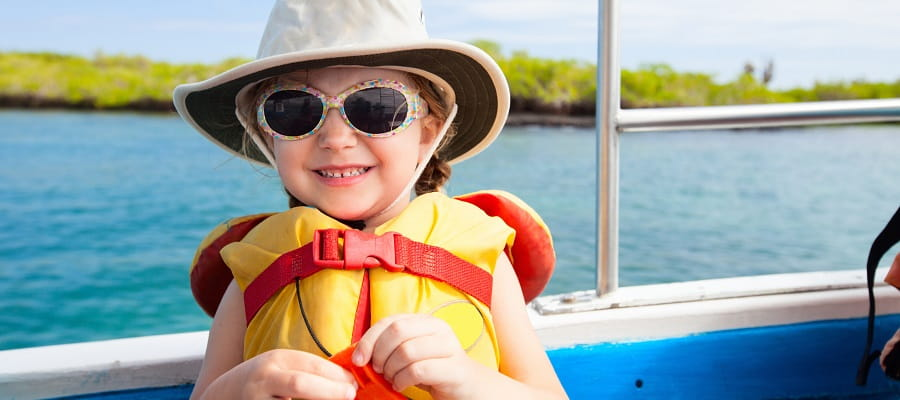 young girl on boat wearing hat, sunglasses and lifejacket