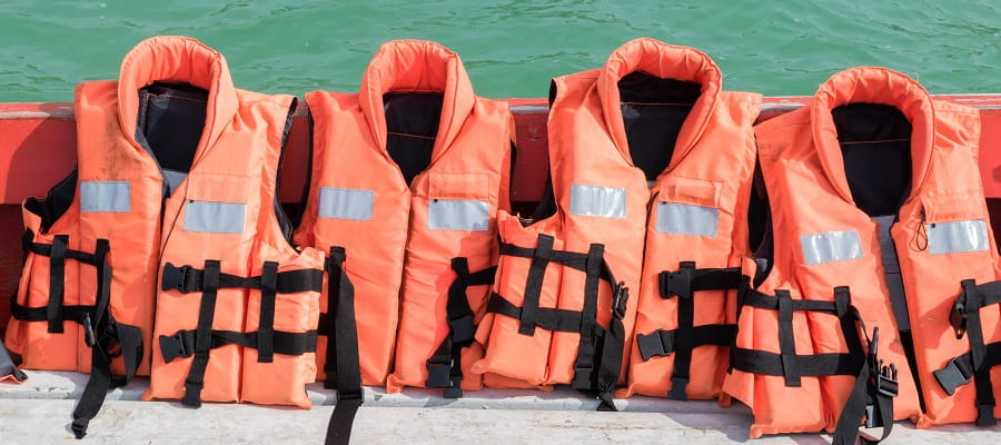 four lifejackets lined up on the edge of a boat
