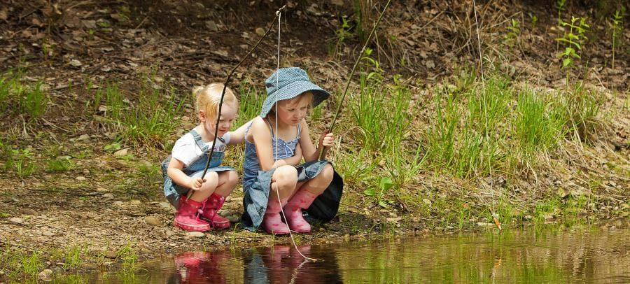 two little girls fishing by a river