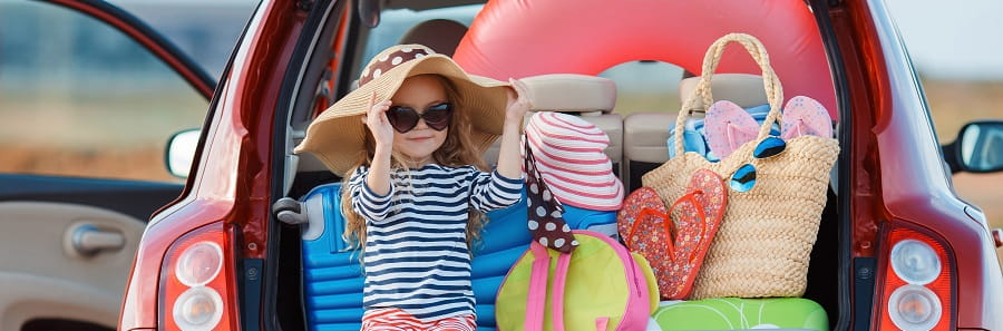 little girl wearing hat and sunglasses sitting in the open boot of a hatchback